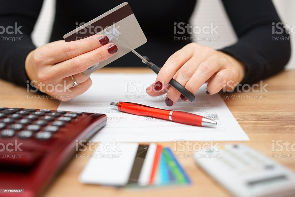 woman is cutting credit card or bank card with scissors stock photo