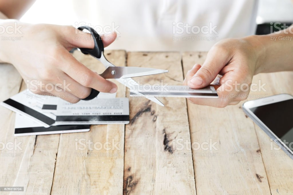 woman is cutting credit card with scissors stock photo