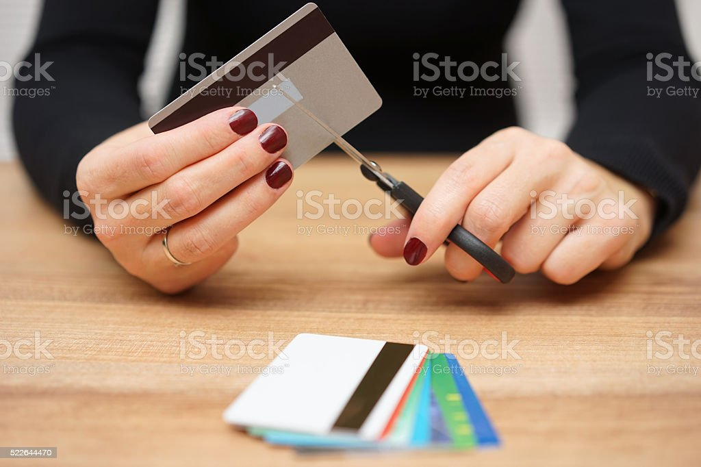 woman is destroying  credit cards because of big debt stock photo