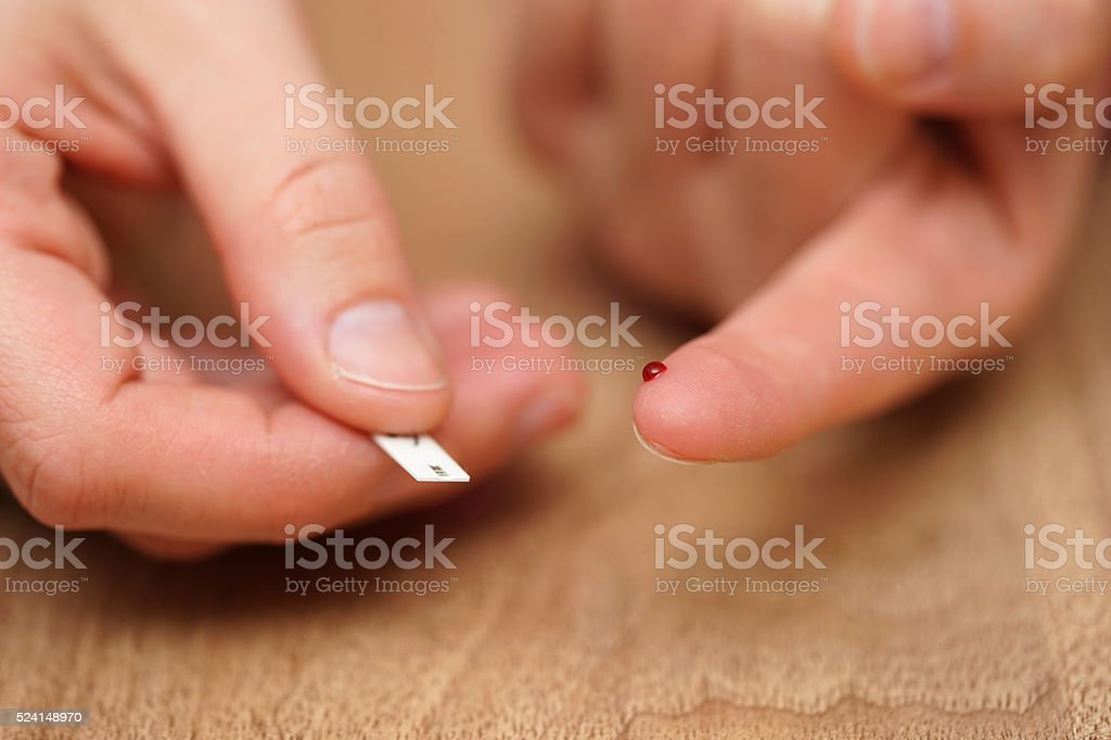 Woman is doing blood sugar test stock photo