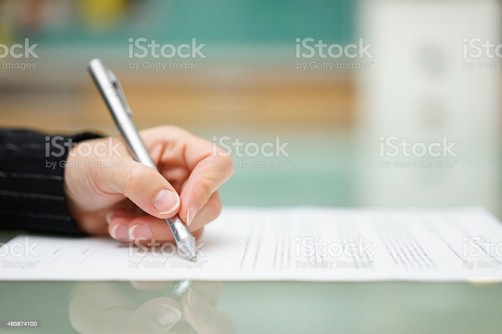 woman is filling document on glass table, shallow depth offield stock photo