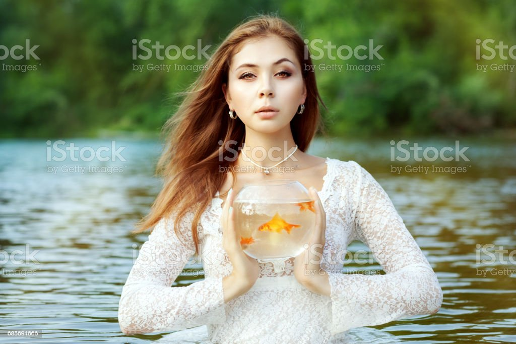 Woman is holding a goldfish in an aquarium. stock photo