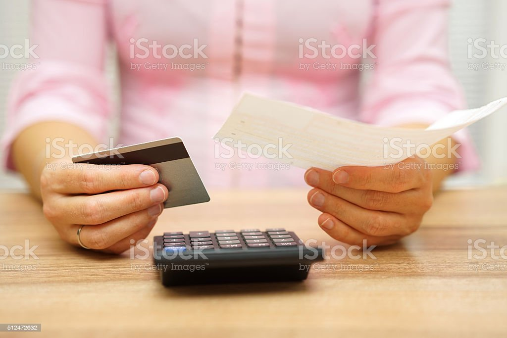 woman is holding bill and credit card in hands stock photo