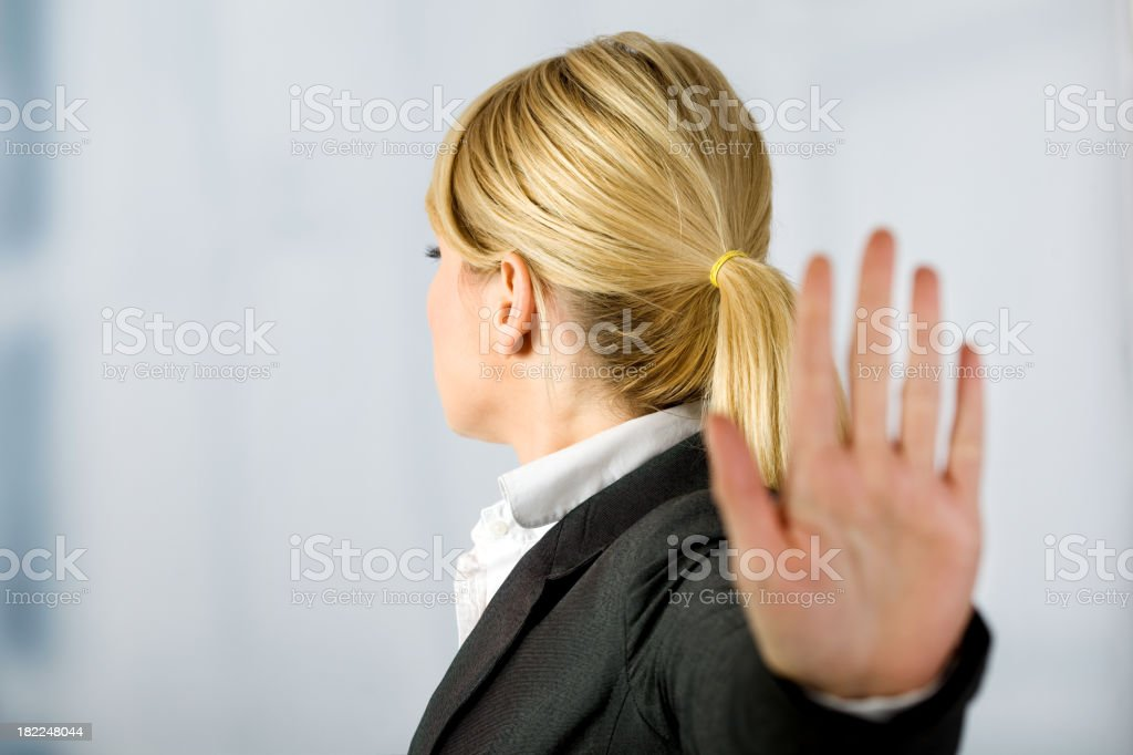 A woman is holding her hand up stock photo