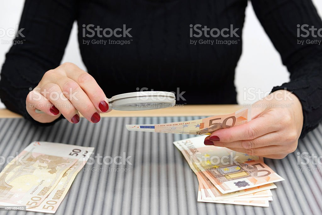 woman is looking through a magnifying glass for counterfeit money stock photo