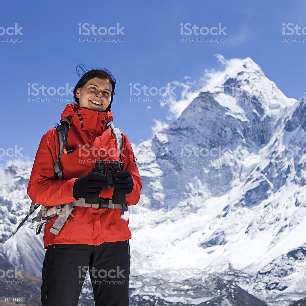 Woman is looking through binoculars in Mount Everest National Park royalty-free stock photo