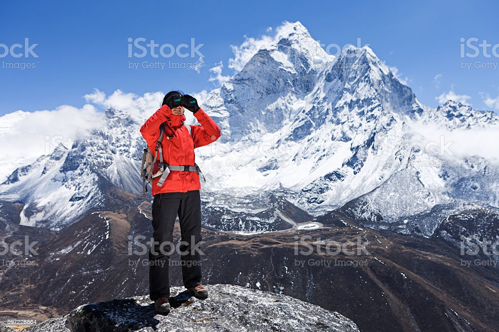Woman is looking through binoculars in Mount Everest National Park stock photo