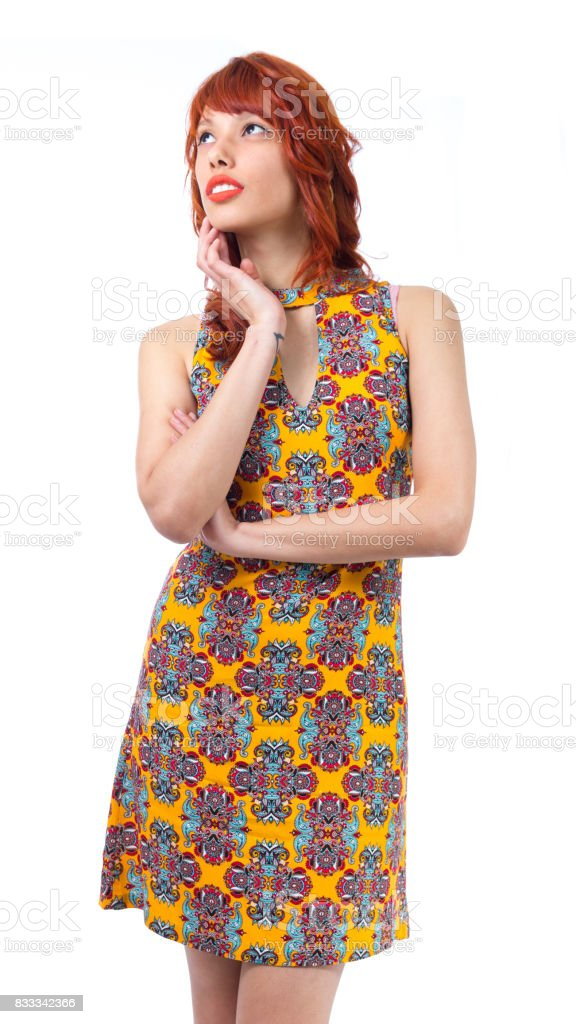 Woman is looking to the side. She is beautiful. Redhead girl wearing yellow and colorful dress. Floral pattern. Fashion and style. Summer and tropical climate. stock photo