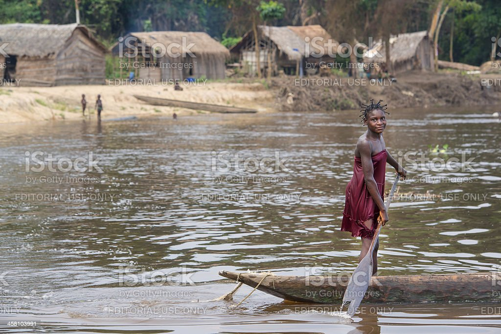 Woman is paddling in a pirogue on Congo River royalty-free stock photo