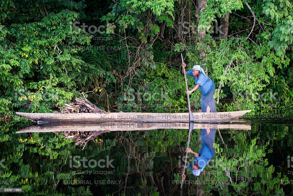 Woman is paddling in a pirogue on Congo River stock photo