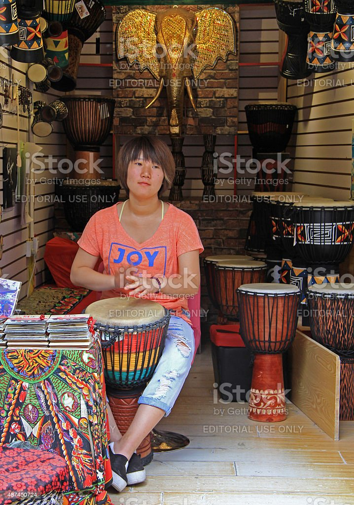 woman is playing drum on the street in Lijiang, China stock photo