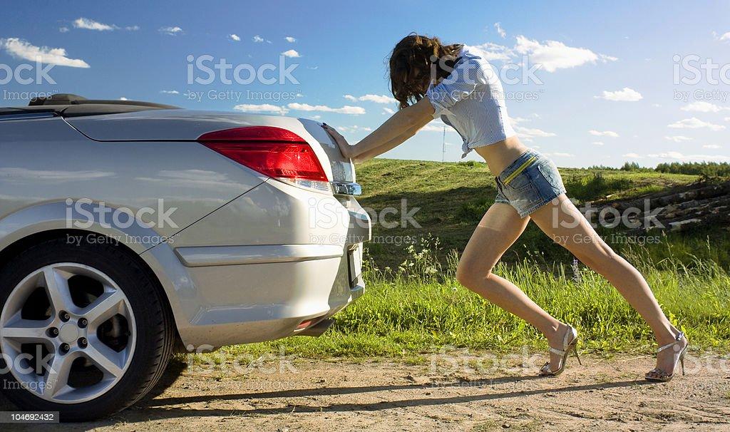 Woman is pushing broken car stock photo