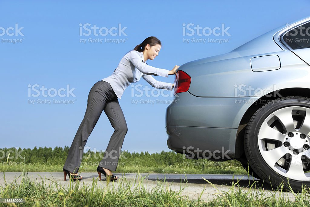 Woman is pushing her car. royalty-free stock photo