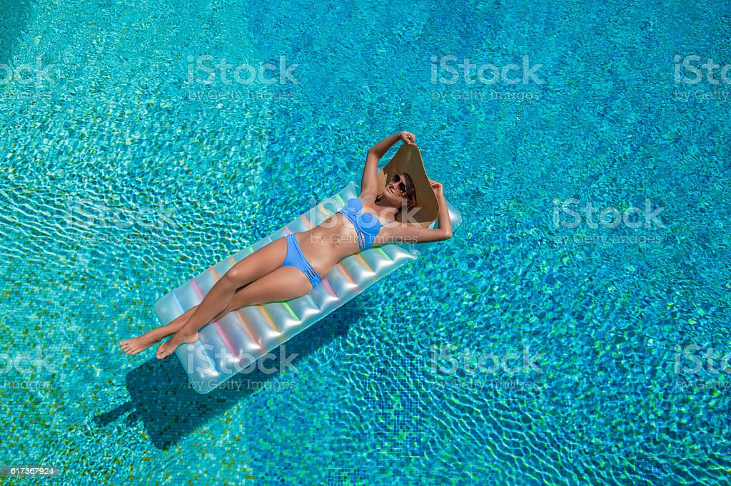 Woman is Relaxing in a swimming pool stock photo