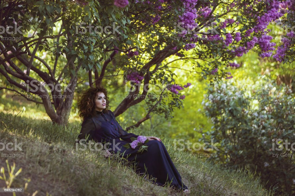 Woman is resting under a lilac bush in the park. stock photo