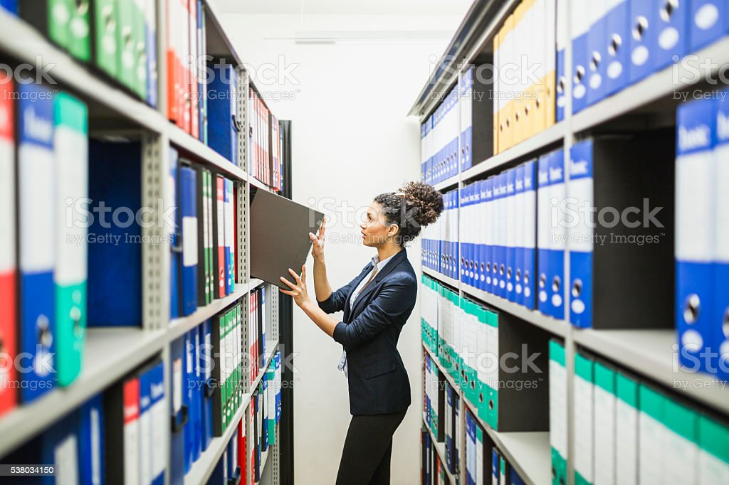 Woman is searching for files in paper archive stock photo