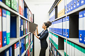 Woman is searching for files in paper archive
