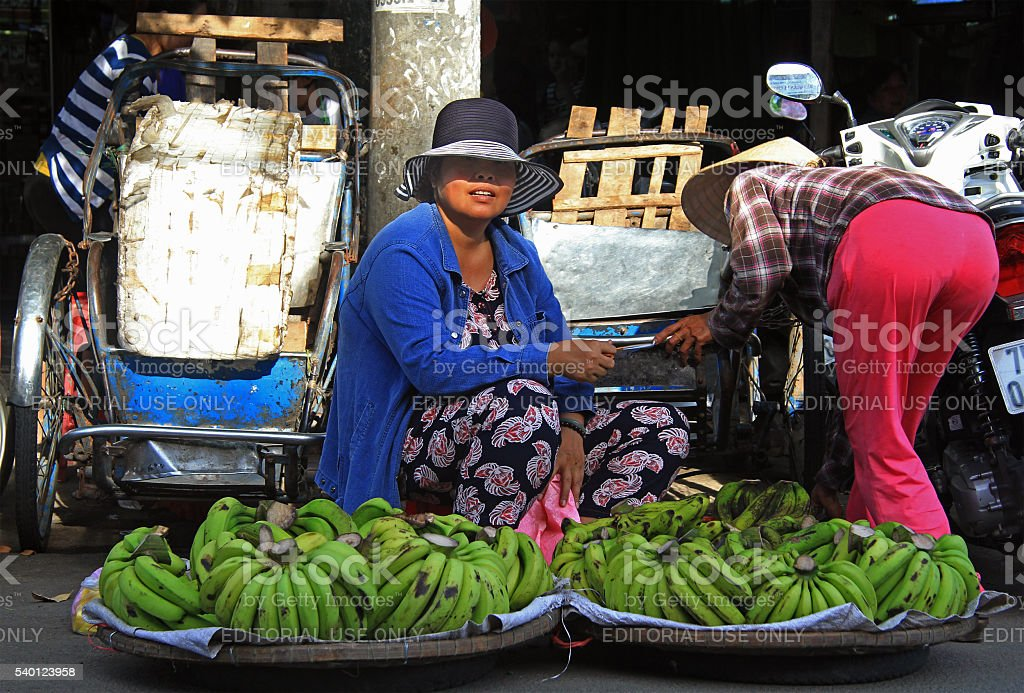 woman is selling bananas on street market in Hue, Vietnam stock photo