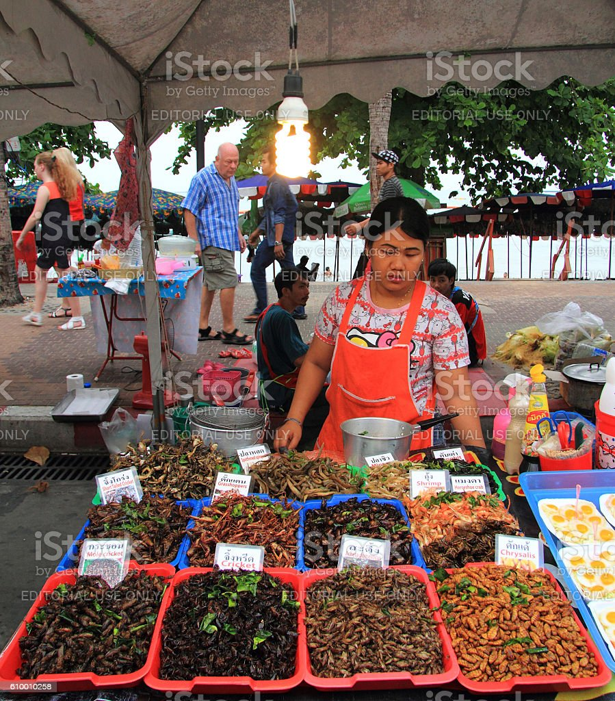 woman is selling fried insects on the market stock photo