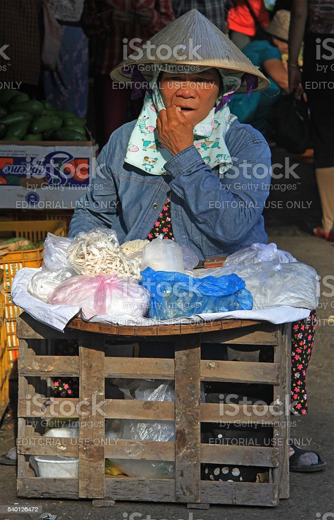 woman is selling something on street market in Hue, Vietnam stock photo