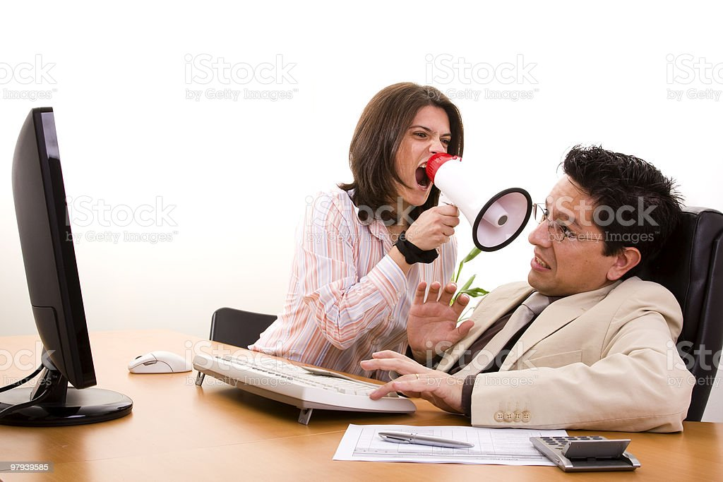 A woman is shouting at a man with a loudspeaker royalty-free stock photo