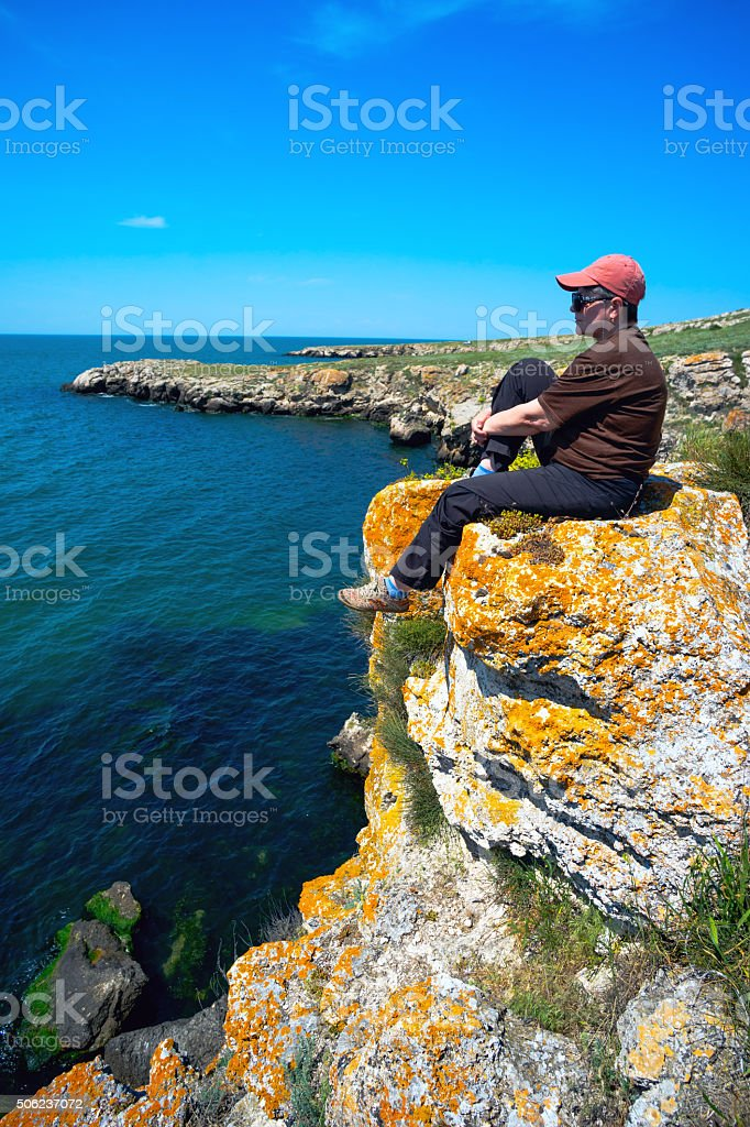 woman is sitting around on  steep shore of the sea . stock photo