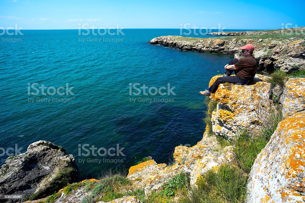 woman is sitting around on the steep shore of  sea stock photo
