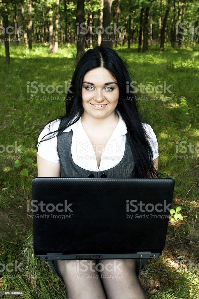 Woman is sitting in the forest with laptop royalty-free stock photo
