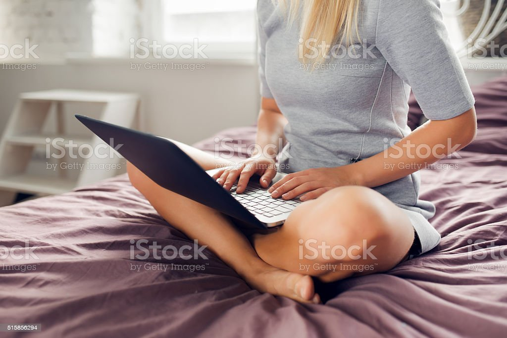 Woman is sitting on bed with a laptop stock photo