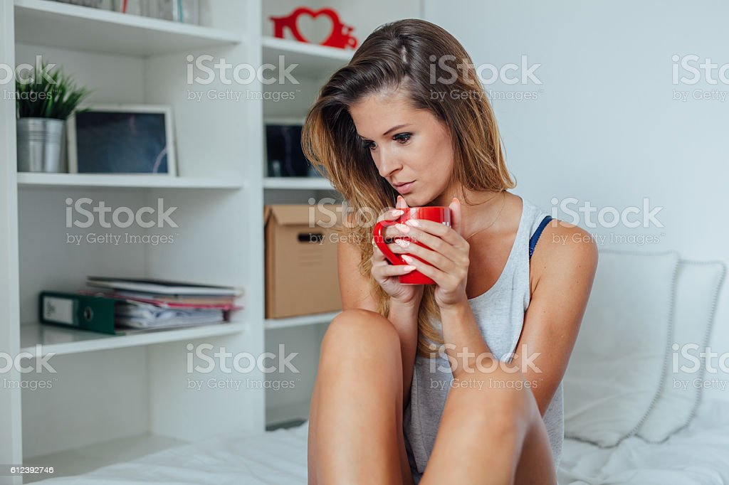 Woman is sitting on the bed and holding a mug. stock photo