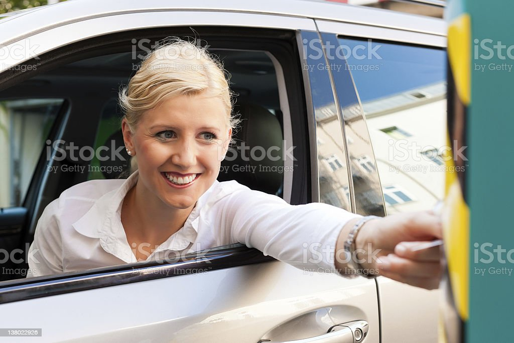 Woman is slipping parking ticket into barrier of garage royalty-free stock photo
