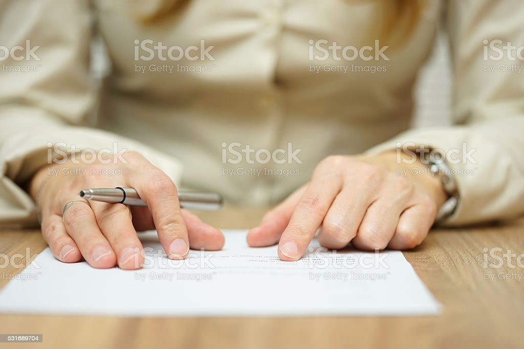 woman is slowly examining legal or financial document stock photo