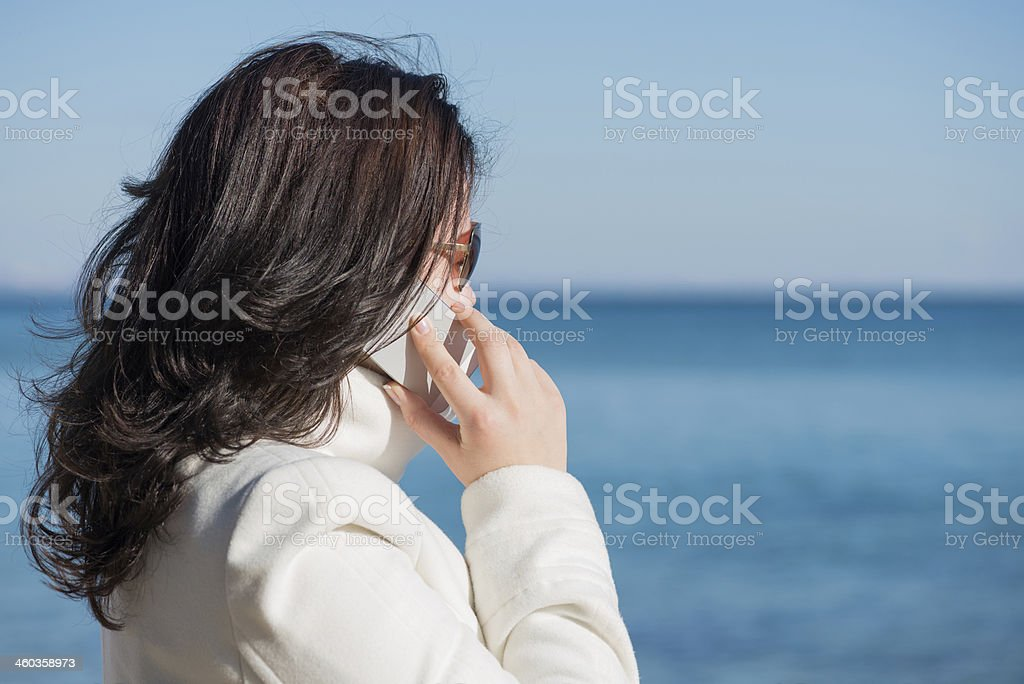 Woman is speaking by mobile phone at the seaside stock photo
