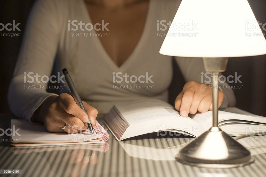 woman is studying and take notes late at night stock photo