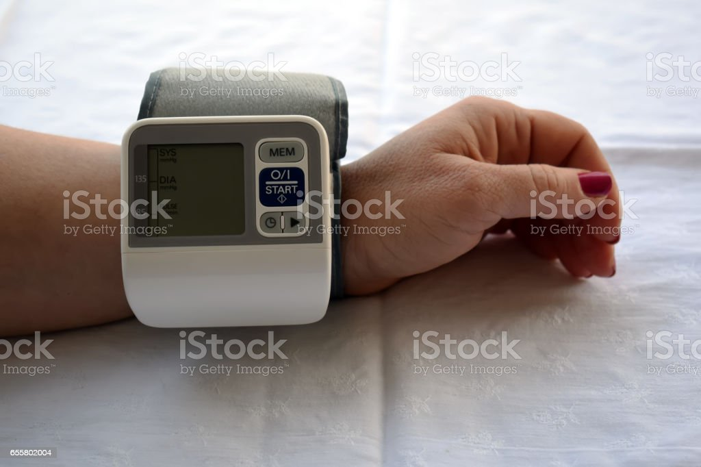 Woman is taking care for health with hearth beat monitor and blood pressure stock photo