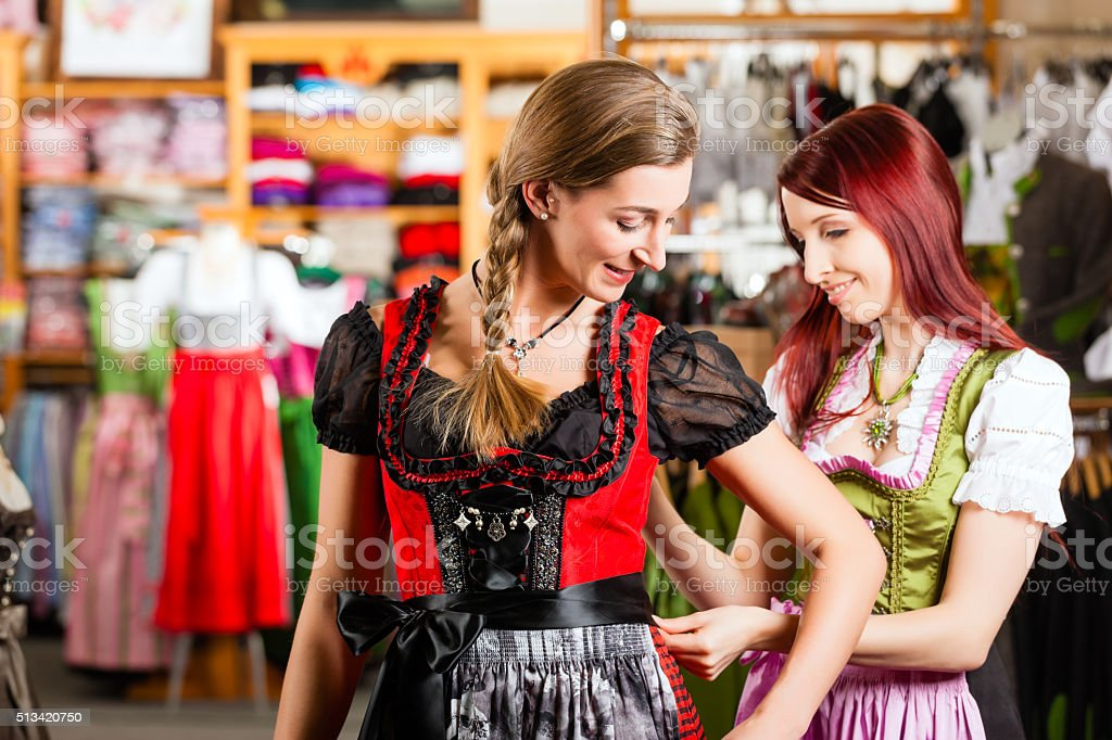 Woman is trying Tracht or dirndl in a shop stock photo
