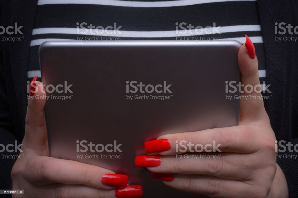 Woman is viewing her tablet in her manicured hands close up stock photo