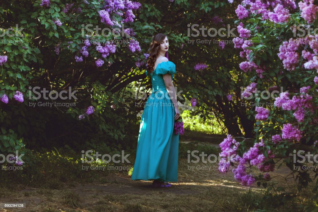 Woman is walking in the garden of lilac. stock photo
