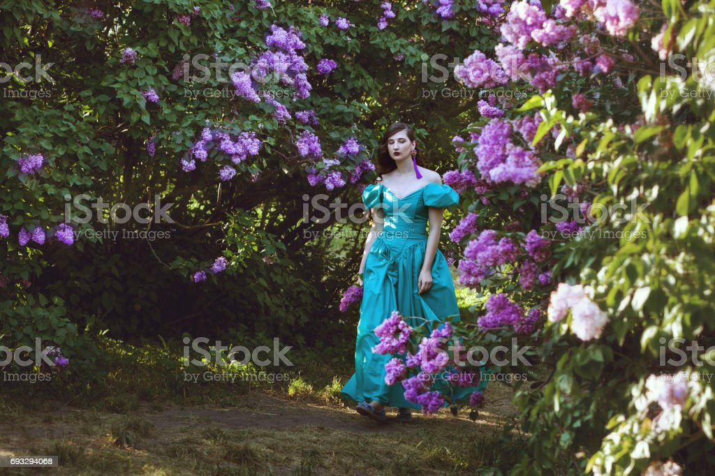 Woman is walking in the park of lilac. stock photo