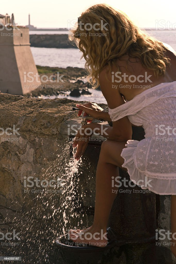Woman is washing hes feets in a public standpipe stock photo