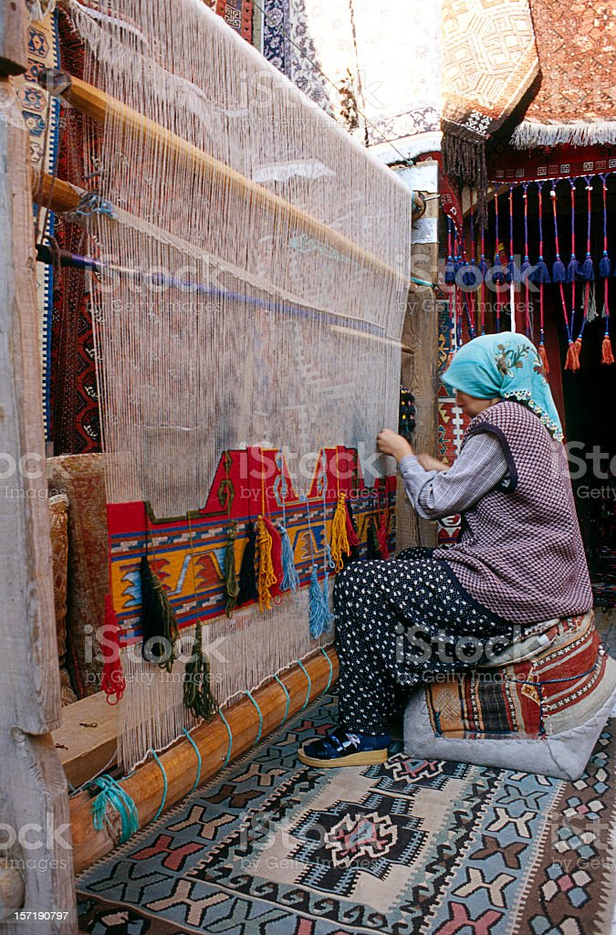 Woman is weaving traditional Turkish carpet in her house stock photo