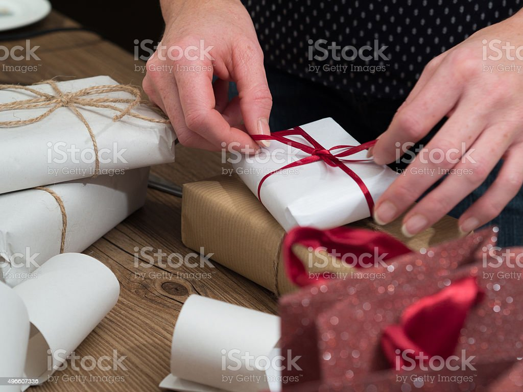 Woman is wrapping christmas gifts stock photo