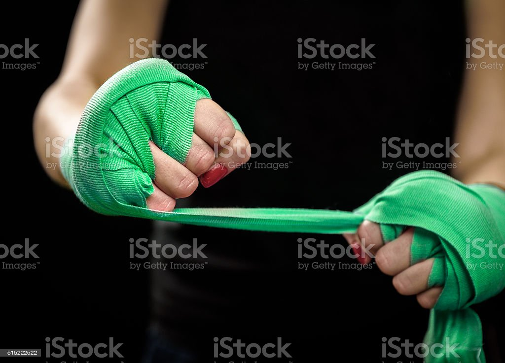 Woman is wrapping hands with green boxing wraps stock photo