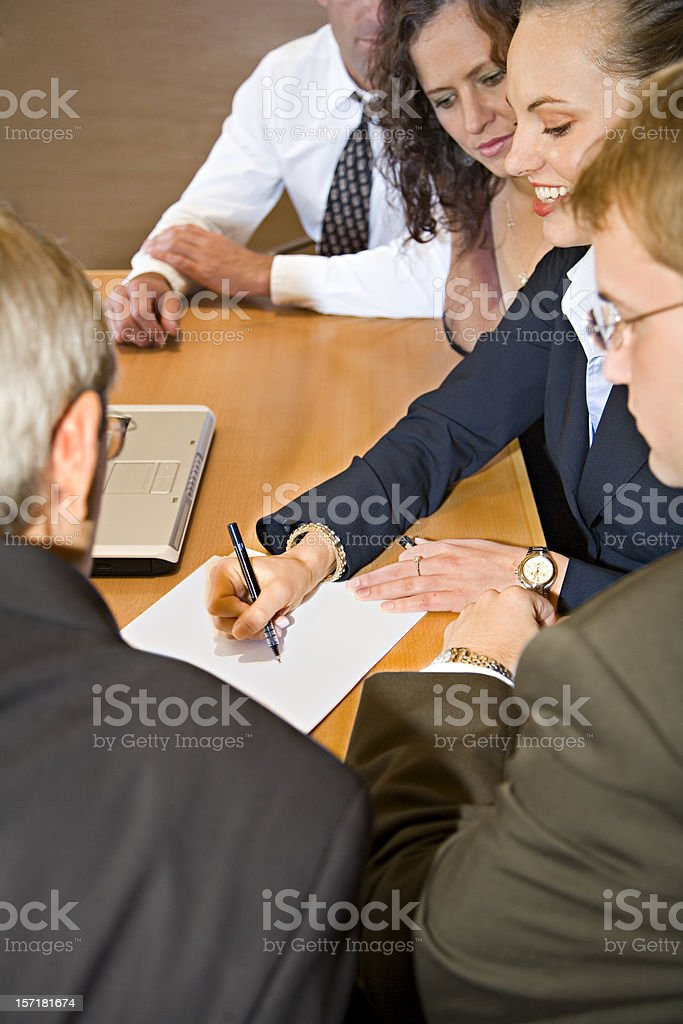A woman is writing at a business meeting stock photo