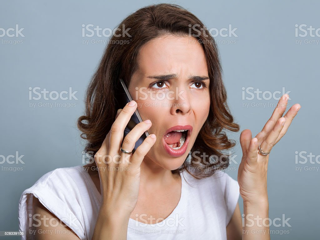 Woman is yelling at phone stock photo