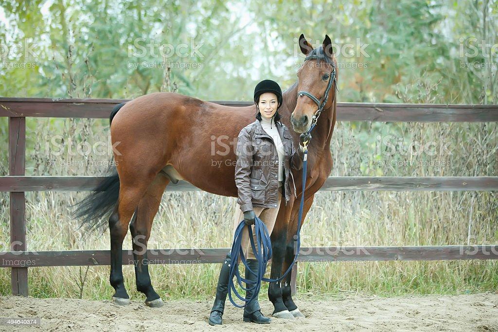Woman jockey is riding the horse outdoor stock photo