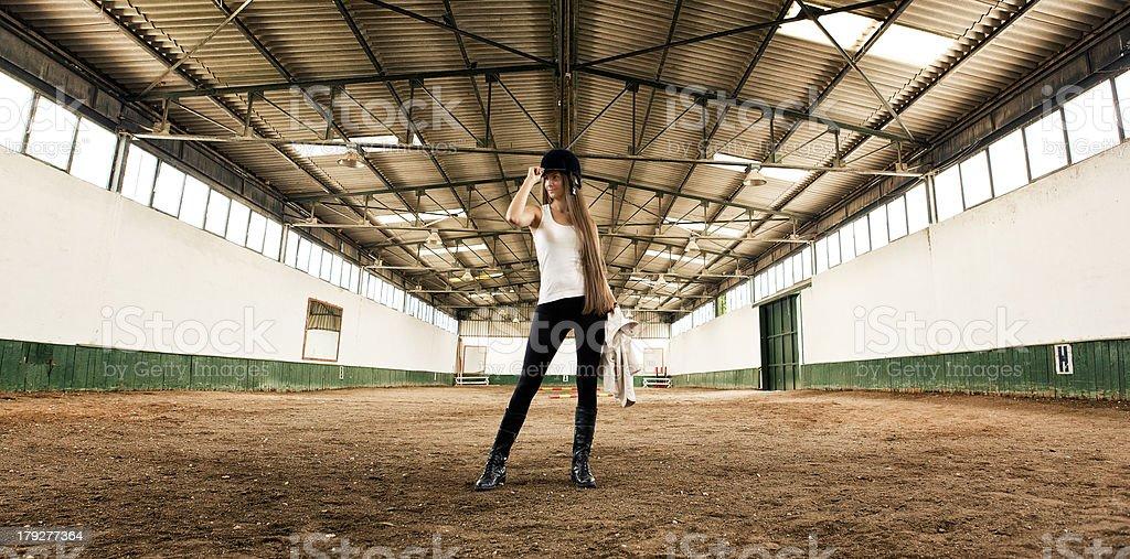 woman Jockey standing Indoor Horse Arena stock photo