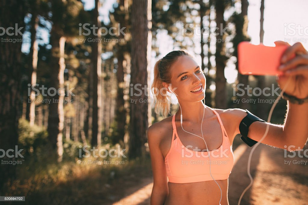 Woman jogger taking a selfie on morning nature trail run stock photo