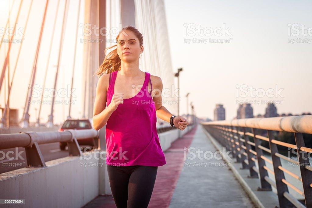 Woman jogging across the bridge stock photo