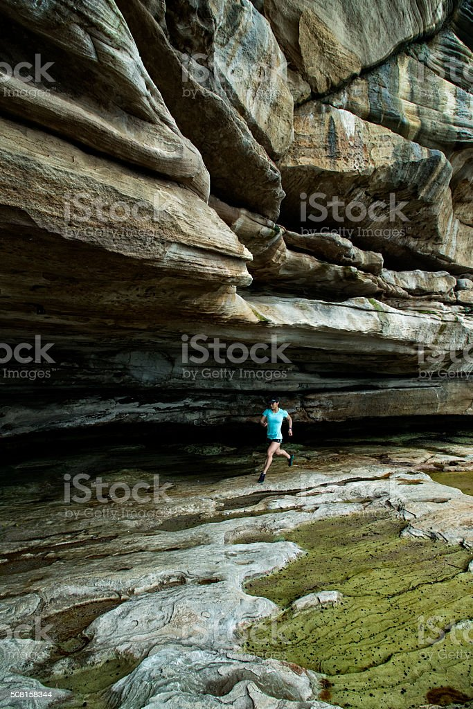 Woman Jogging by Cliffs stock photo